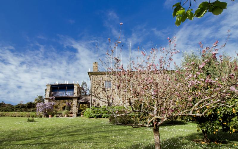 Fachada y jardín de la casa de indiano