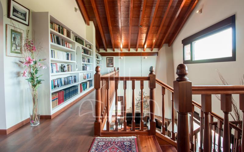 Biblioteca y barandilla de madera en vivienda unifamiliar en el Valle de Ayala, Menagarai